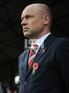 Uwe Rosler, right, German manager of Brentford wears a poppy and observes a minute's silence for Remembrance Day